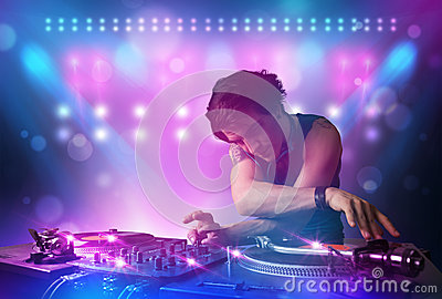 Disc jockey mixing music on turntables on stage with lights and Stock Photo