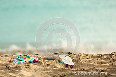 Discarded flipflops on sandy beach by ocean