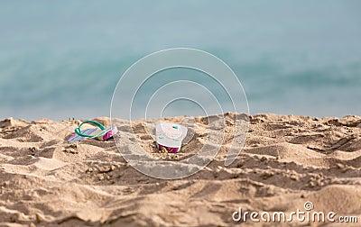 Discarded flipflops on sandy beach by ocean