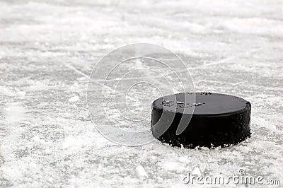 Disco di gomma di hokey nero sulla pista di pattinaggio di ghiaccio