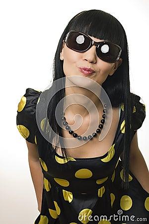 The disco girl in sun glasses sends an air kiss
