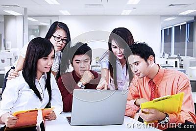 Discusión del equipo del negocio sobre el ordenador portátil en la oficina