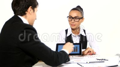 Discussion between a businessman and businesswoman. It shows the graphics tablet. . It shows the graphics tablet. scattered on the table stationery, developing stock video footage