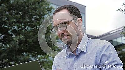 Discussion vidéo en ligne sur un ordinateur portable par un homme d'affaires assis à l'extérieur clips vidéos