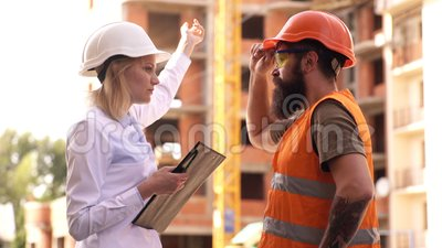 Discuta el proyecto del progreso Inspector y constructor brutal barbudo discutir progreso de la construcción Proyecto de construc almacen de metraje de vídeo