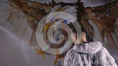 Diseñador artístico dibuja un águila en la pared El decorador artesano pinta una imagen con color de aceite acrílico pintor pinto almacen de video