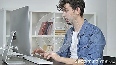Diseñador creativo joven Leaving Office después de trabajar en la mesa almacen de video