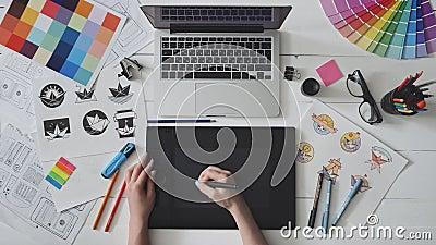 Diseñador creativo que usa la tableta de gráficos mientras que trabaja en su tabla metrajes