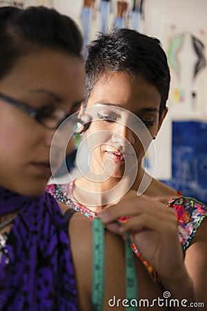 Diseñador de moda que usa la cinta de medición con el cliente