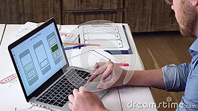 Diseñador de UX que crea el prototipo móvil del app en su ordenador portátil metrajes