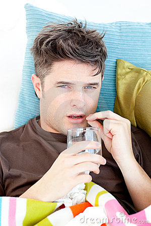 Diseased caucasian man taking pills with water