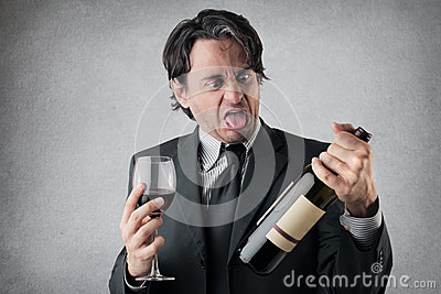 Disgusted businessman with a glass of wine