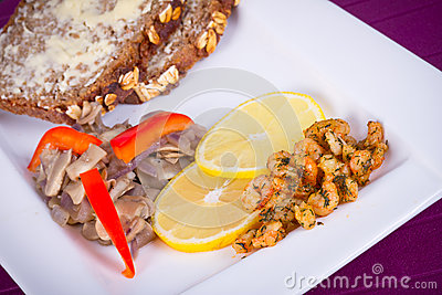 Dish with fried prawns, bread and lemon