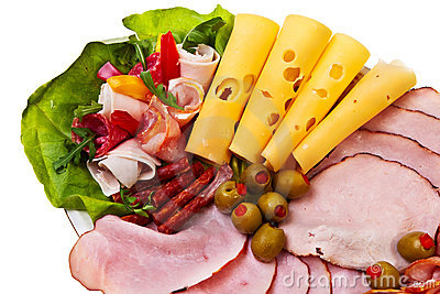 Dish with sliced smoked ham, salami rolls.