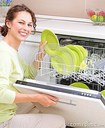 Dishwasher. Young woman doing Housework