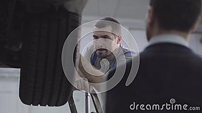 Disparos sobre el hombro de un trabajador serio mirando las ruedas del auto Mecánica automática comprobando el automóvil fijo jun almacen de metraje de vídeo