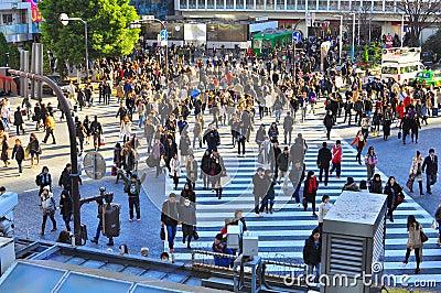 Dispersiones de la muchedumbre en el paso de cebra en calle muy transitada Imagen editorial