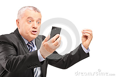 A displeased manager in suit screaming on a mobile phone