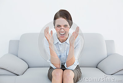 Displeased well dressed woman screaming on sofa