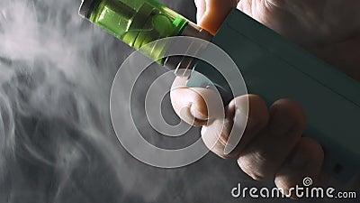 Dispositivo di Vape - RDA e MOD mech in mano maschio con un gran numero di nuvole o di vapore del vapore stock footage