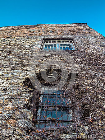 Distorted wall of an old stone building with two bar window pane