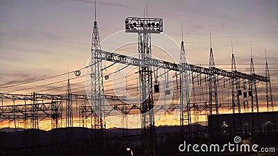 Distribución de subestaciones eléctricas con líneas eléctricas y transformadores contra el hermoso cielo de puesta de sol almacen de metraje de vídeo