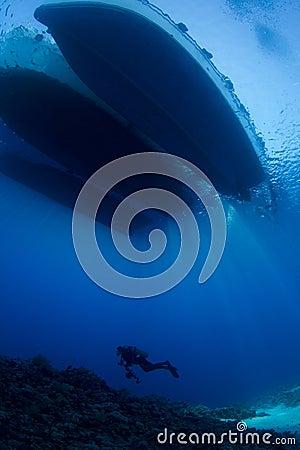 Scuba Diver below boat underwater scene