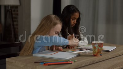 Diverse schoolgirls painting with watercolors stock footage