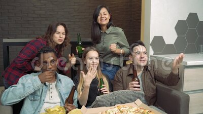 Diversi amici guardano la TV e girano duro per il loro team preferito a casa video d archivio