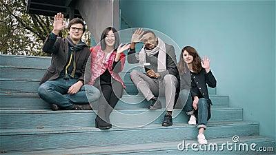 Diverso gruppo di amici che ondeggiano le mani che si siedono le scale del ou archivi video