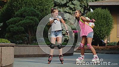 Divertente danza tra due ragazze che patteggiano a rotelle in un parco cittadino archivi video