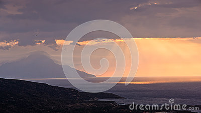 Divine light, stormy sky and sunrise on a landscape around saint mountain Athos