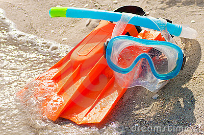 Diving mask, snorkel and fins on a sandy beach