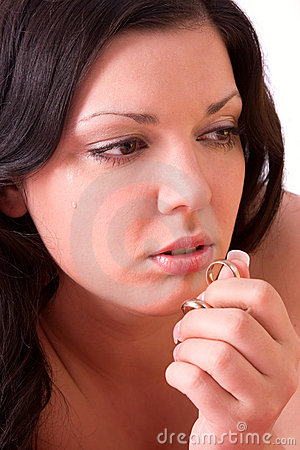 Divorce. Sad woman holding gold wedding ring.