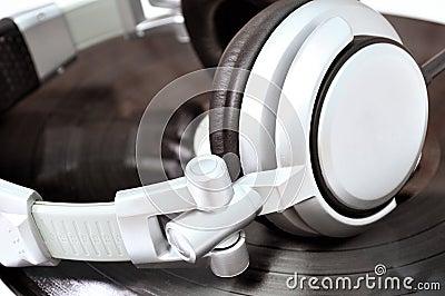 DJ headphones lying over black vinyl