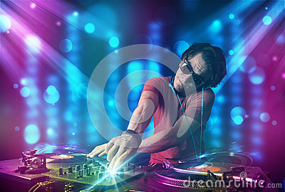 Dj mixing music in a club with blue and purple lights Stock Photo