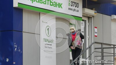 Man wear face masks and latex gloves is standing at ATM next to Privat bank stock footage