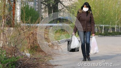 People walk along city street and wear face masks and latex gloves. Quarantine stock video