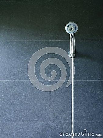 Doccia del bagno sulla parete nera delle mattonelle fotografia ...
