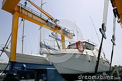 Dock crane elevating a fishing boat
