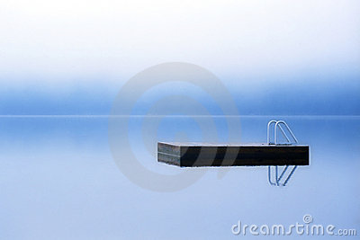 Dock floating on misty lake