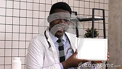 Docteur africain sérieux beau présent le produit sur l'écran de comprimé Affichage blanc clips vidéos