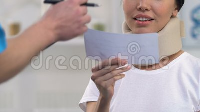 Docteur donnant la prescription à la femme de sourire dans le collier cervical de mousse, assurance banque de vidéos