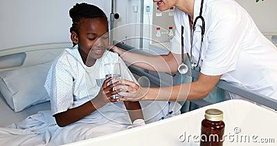 Docteur féminin donnant la médecine à la fille malade banque de vidéos
