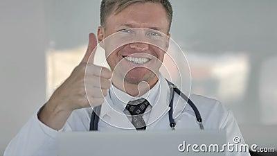 Docteur heureux Gesturing Thumbs Up dans la clinique clips vidéos