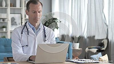 Docteur supérieur Working On Laptop dans la clinique banque de vidéos