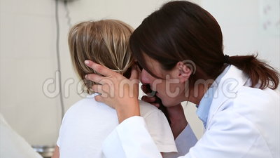 Doctor auscultating the ear of a child. In examination room stock footage