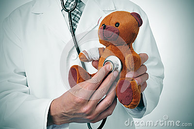 Doctor auscultating a teddy bear with bandages in its head and a