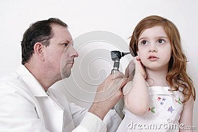 Doctor checking little girl s ear