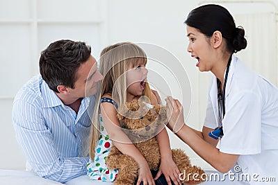 Doctor checking little girl s throat